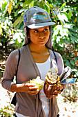 Woman holding a cocoa pod split open
