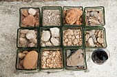 A collection of different types of soil and stones, with a glass of red wine (wine region of Corbieres, France)