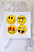 Four cookies decorated with funny smiley faces