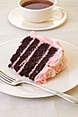 Slice of Chocolate Layer cake with raspberry frosting on a white plate