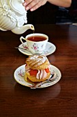 Cream puff pastry with strawberries being served with tea