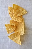 Several tortilla chips on a white background (top view)