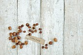 Hazelnuts with a brown paper label on a wooden background (top view)