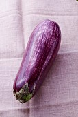 An aubergine on a linen cloth