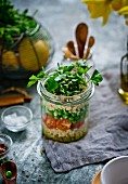 Millet salad with tomatoes and peas in a glass jar