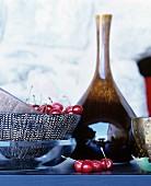 Still-life arrangement of bowls, vase and cherries