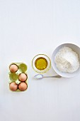 Ingredients for pasta dough: eggs, oil, salt and flour (seen from above)