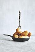 Rohe ungeschälte Kartoffeln mit Gabel in Bratpfanne