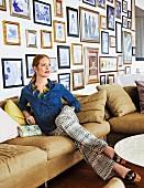 Rothaarige Frau in Jeanshemd, gemustertem Jumpsuit und Plateau-Sandaletten auf einer Couch