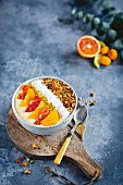 A smoothie bowl with citrus fruits and coconut flakes