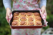 Woman holding cinnamon rolls in a baking tray in a garden