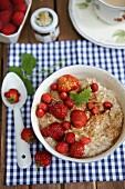 Sommer-Porridge mit Erdbeeren auf Gartentisch