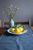 Zitronen auf weißem Teller vor Blumenvase auf Tisch