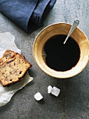 Black coffee in rustic cup with pecan and date cake slices