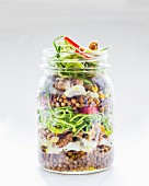 Vegetable salad with lentils and courgette in a glass jar