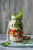 Salad jar for work lunch with giant cous cous, roasted vegetables, salad and yoghurt tahini and smoked paprika dressing