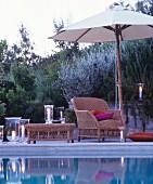 Romantische Abendstimmung am Pool mit gemütlichem Korbsessel und brennenden Windlichtern
