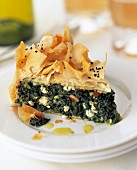 A slice of spinach filo pastry pie on a plate in a table setting