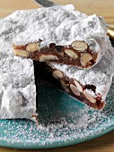 A whole Italian panforte cake with a slice on top