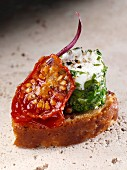 Herb barrelled goats cheese on a green olive croute and spiced tomato canape editorial food