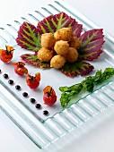Panierte frittierte Mozzarellabällchen dekorativ arrangiert auf Glasplatte