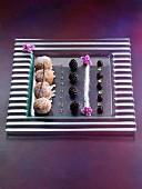 Mini-Donuts dekorativ arrangiert mit Beeren und Blüten auf Glasplatte