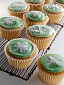 Cupcakes with a white shamrock on top of the green icing