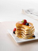 A pile of American pancakes with fruit and honey