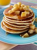 Ein Stapel Pancakes mit Apfelstückchen und Honig