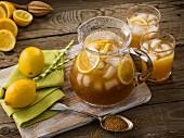 Erfrischende Zitronenlimonade 'Regenwald Brise' mit Eiswürfeln in Krug und Gläsern