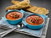 Tomatencremesuppe in Schälchen, dazu Stangenbrot