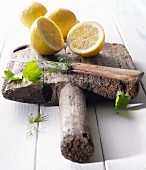 Halved lemons on an old wooden board with parsley, dill and a knife
