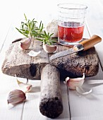 Cloves of garlic with red wine and a knife on an old wooden board