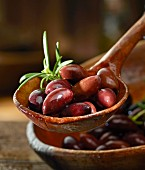 Kalamata olives with rosemary in a wooden ladle