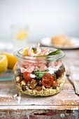 Lunch in a glass jar: shrimp, tomatoes, hazelnuts, rocket and wheat