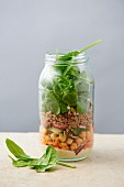 A quinoa salad with houmous and vegetables in a glass jar
