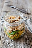 Saffron rice salad with chicken and beans in a glass jar