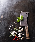 An old meat cleaver with garlic, salt, chilli and basil on a baking tray