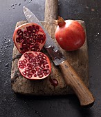 Two pomegranates, whole and halved, with a knife on an old wooden board