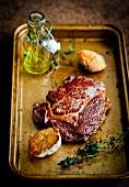 A steak with garlic on a roasting tray