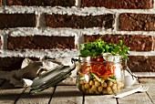 Salad with chickpeas, tomatoes and parsley in a glass jar