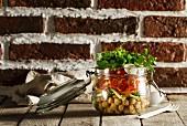 Salat mit Kichererbsen, Tomaten und Petersilie im Glas