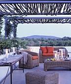Terrasse mit Korbmöbeln und Kerzendeko im Abendstimmung