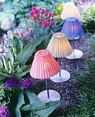 Teelichter mit verschiedenfarbigen Lampenschirmchen als sommerliche Gartendekoration
