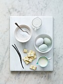 Various baking ingredients: sugar, milk, eggs, vanilla pods, flour and white chocolate