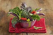 A vegetable bowl containing kale, chillis and long, thin aubergines