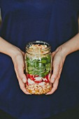 A woman holding a glass jar of layered salad