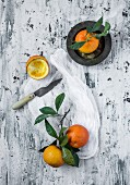 Oranges on light backgroundwith napkin, plates and green leaves