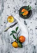 Orangen mit Zweig und Blättern auf weißem Tuch