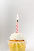A birthday cupcake with a burning candle in front of a white background